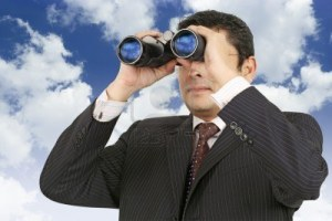 8988525-an-indian-businessman-in-his-late-thirties-looking-through-binoculars-with-a-cloudy-blue-sky-in-the-